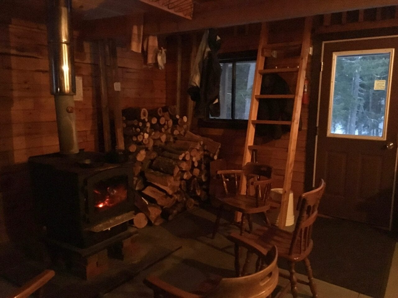 A wood stove and stach of firewood sit inside a rustic cabin.