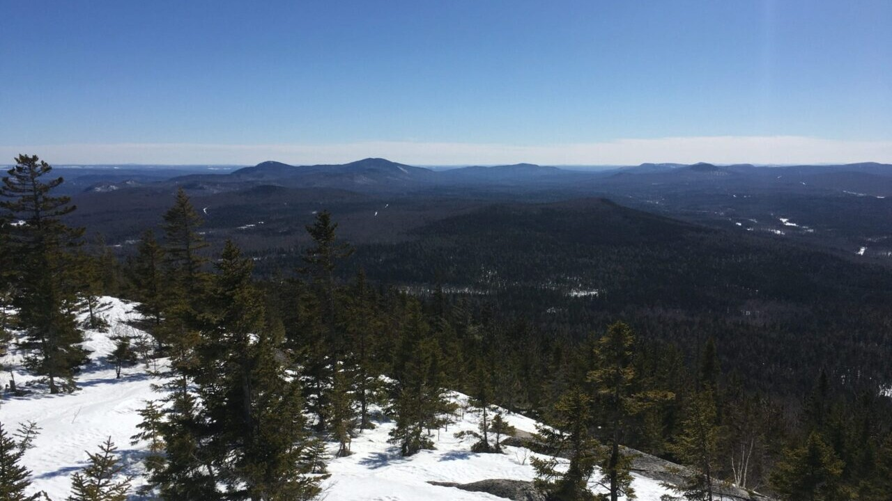 A view showcases snowy forests and distant mountains.