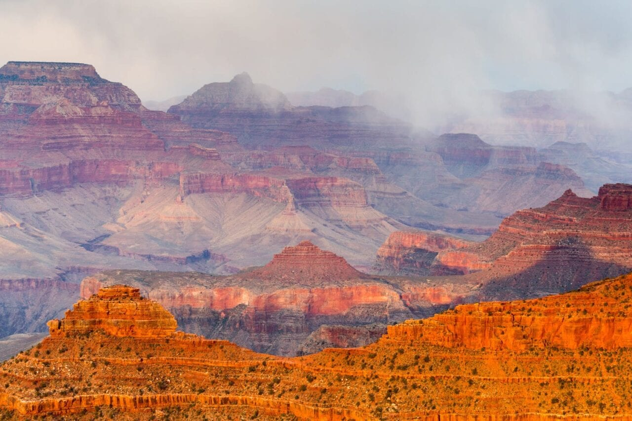 The Grand Canyon is lit with a red glow and mist.