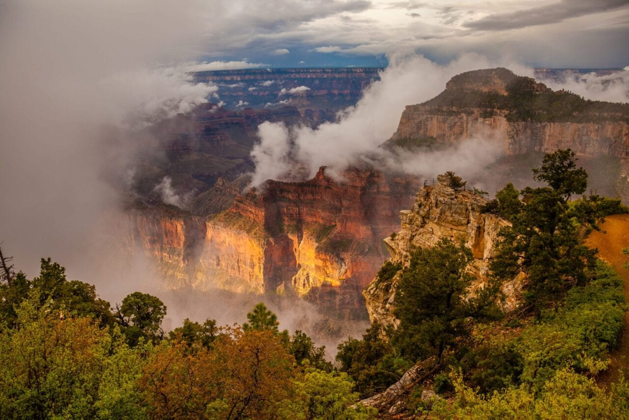 The misty Grand canyon is lit with a morning glow.