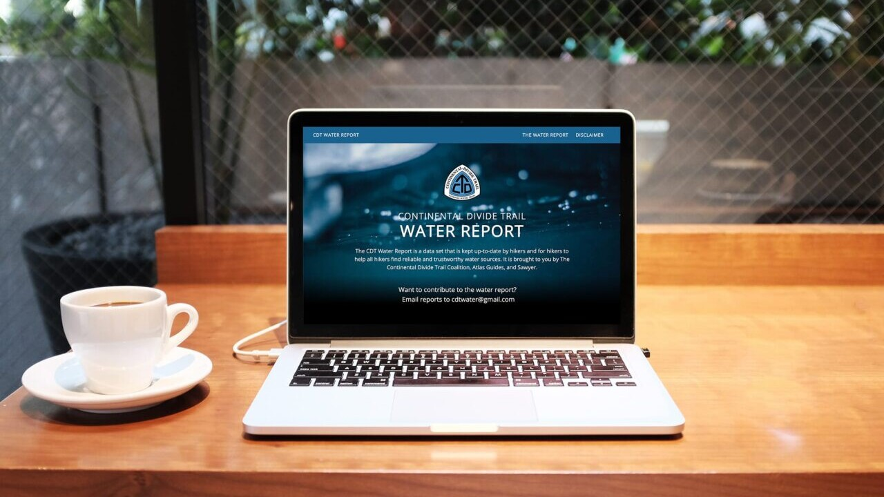 A laptop sits on the table next to a cup of coffee and its screen shows the Continental Divide Trail Water Report website.