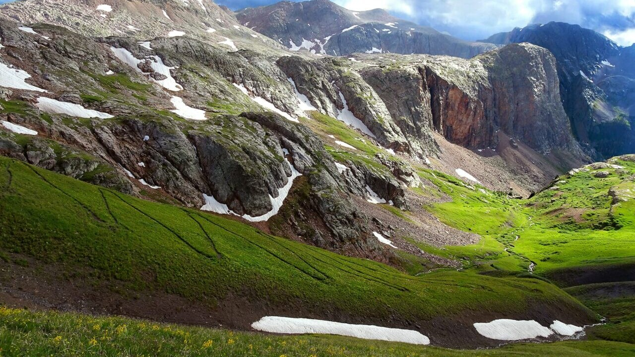 A trail winds down a steep slope to a lush green valley in between tall mountains on the Colorado Trail.