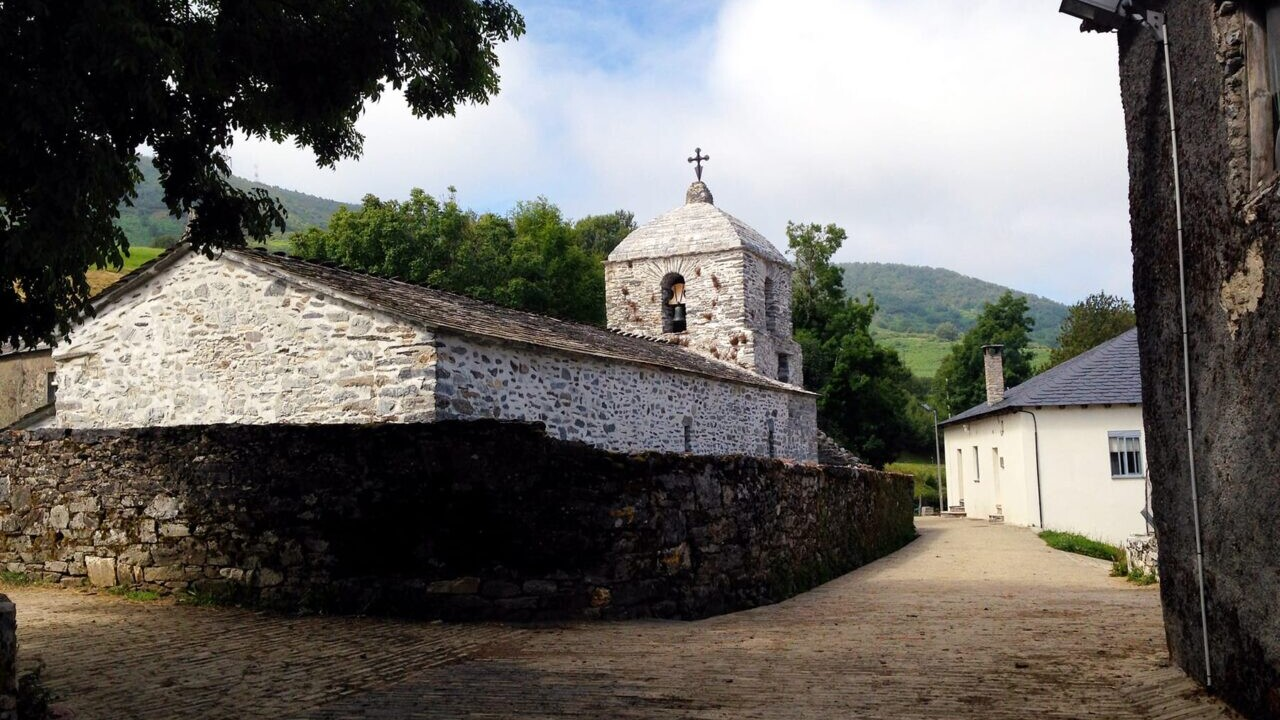 The Camino de Santiago winds through a small town on cobblestone streets with an old, white stone church on the left and green rolling hills in the background.