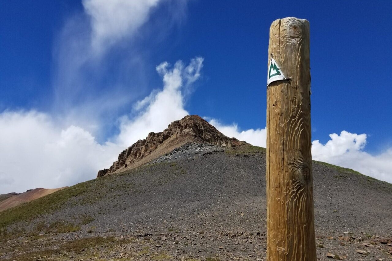 A trail sign stands in front of a rocky mountain peak.