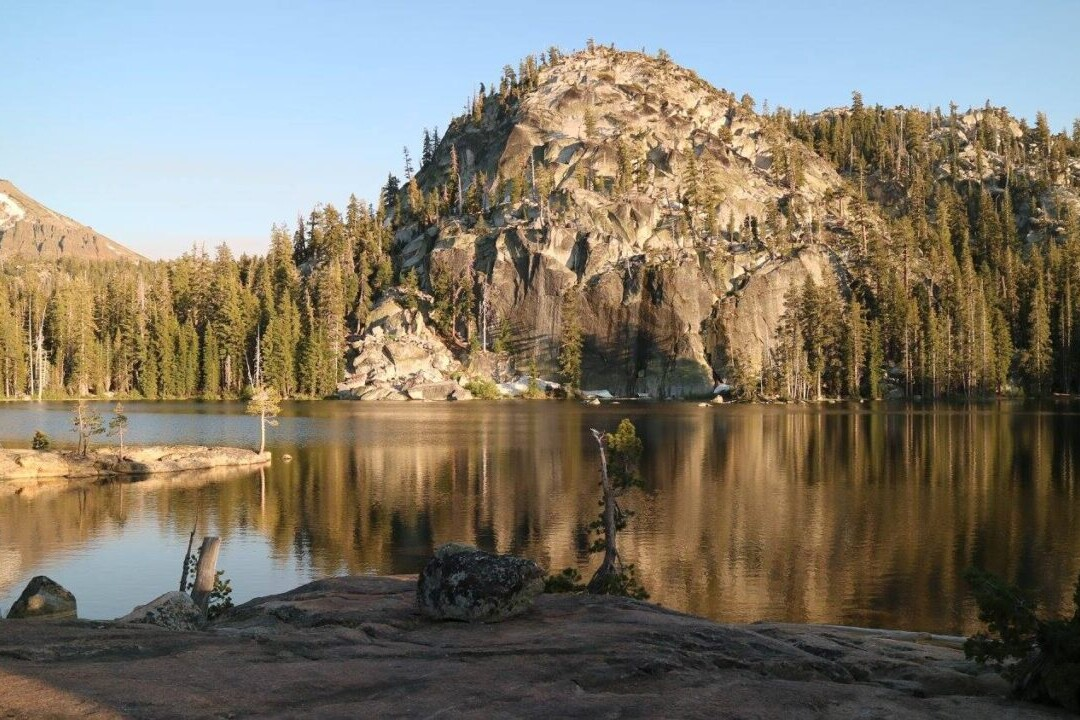 A lake reflects a nearby mountain and trees.