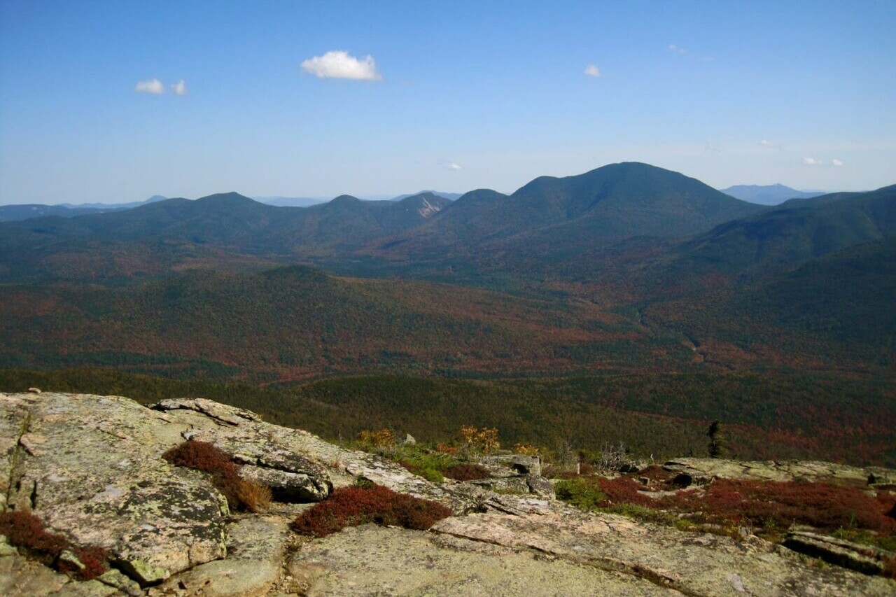 A rocky ridge overlooks distant mountains.