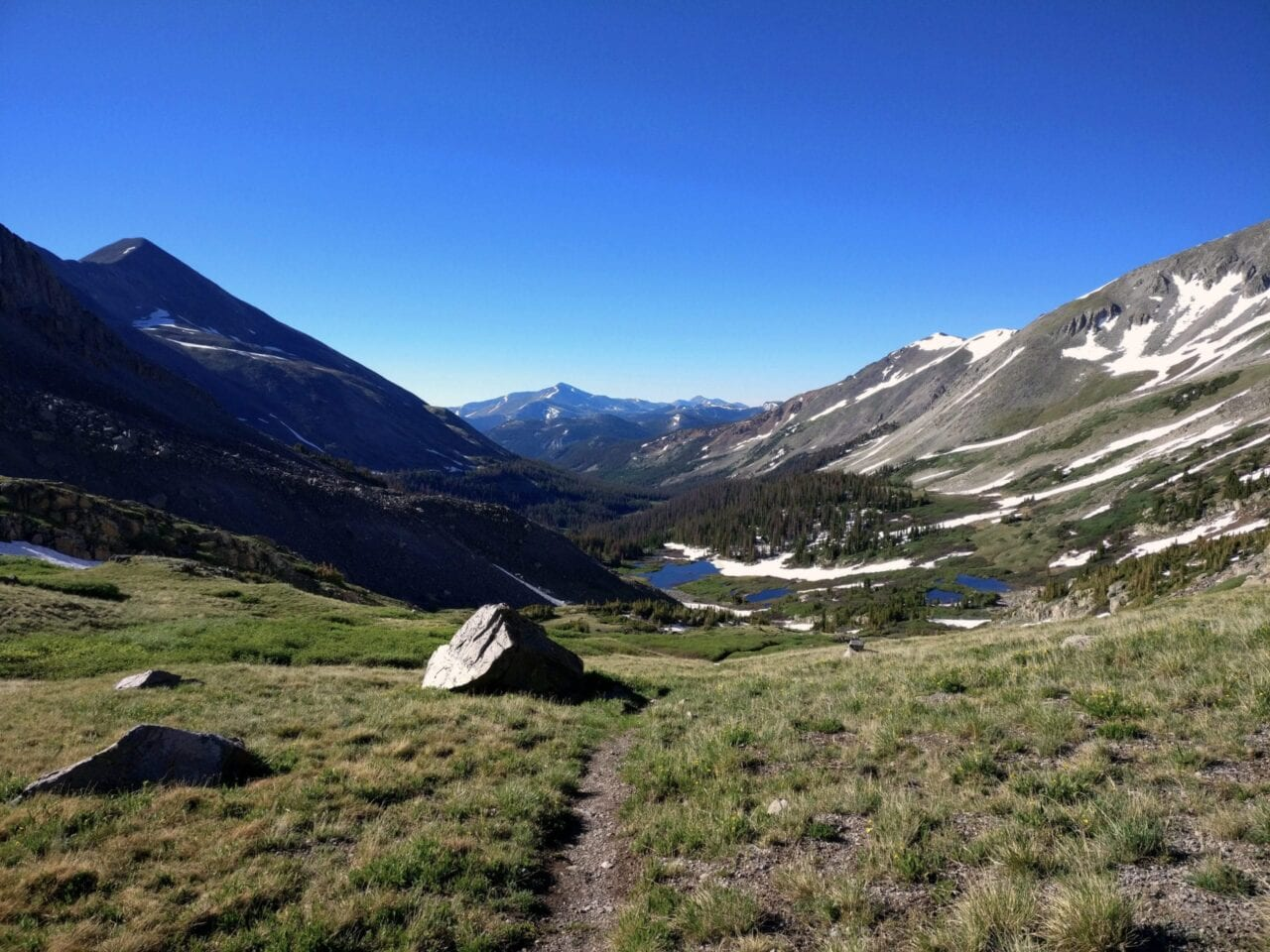 A trail leads through a grassy meadow to distant blue lakes and tall mountains.