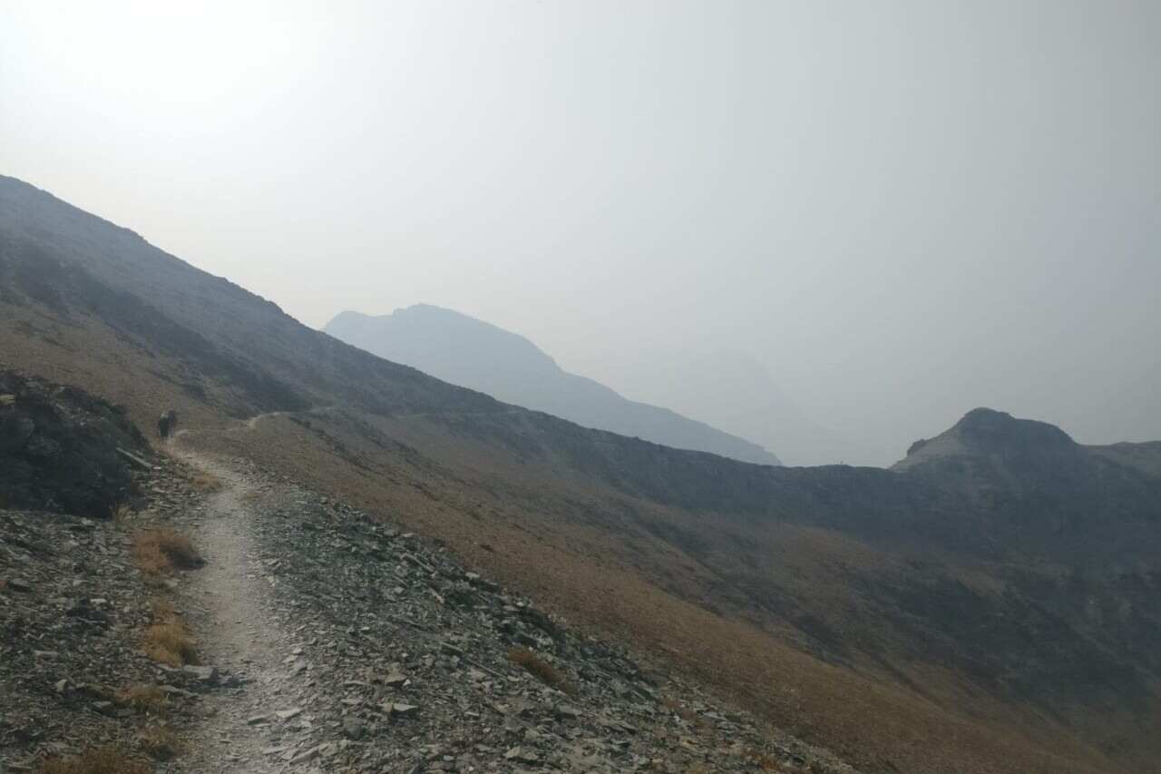 A trail travels along a rocky mountainside towards misty mountains.