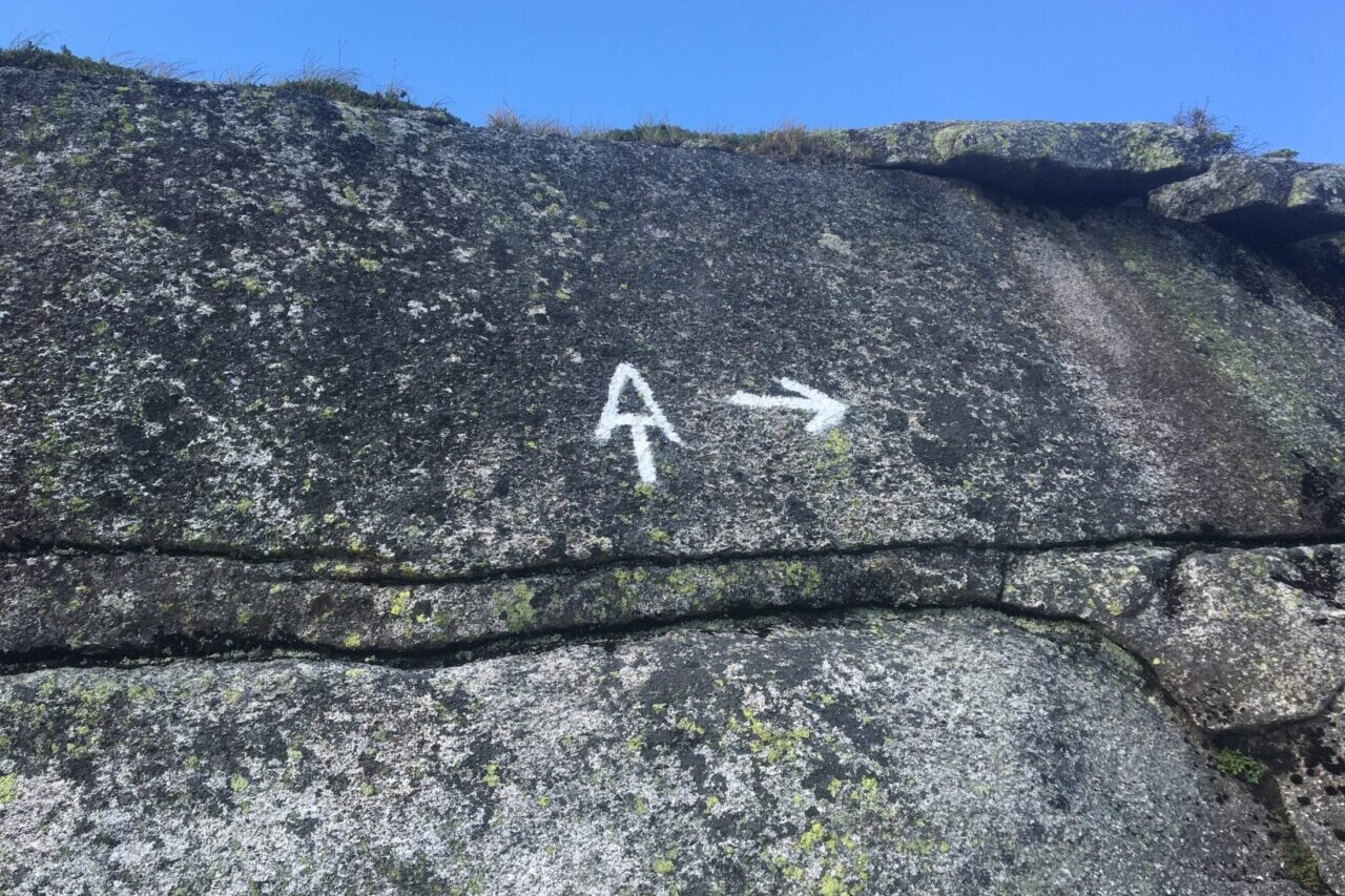 An Appalachian Trail symbol and an arrow are drawn on a rock.