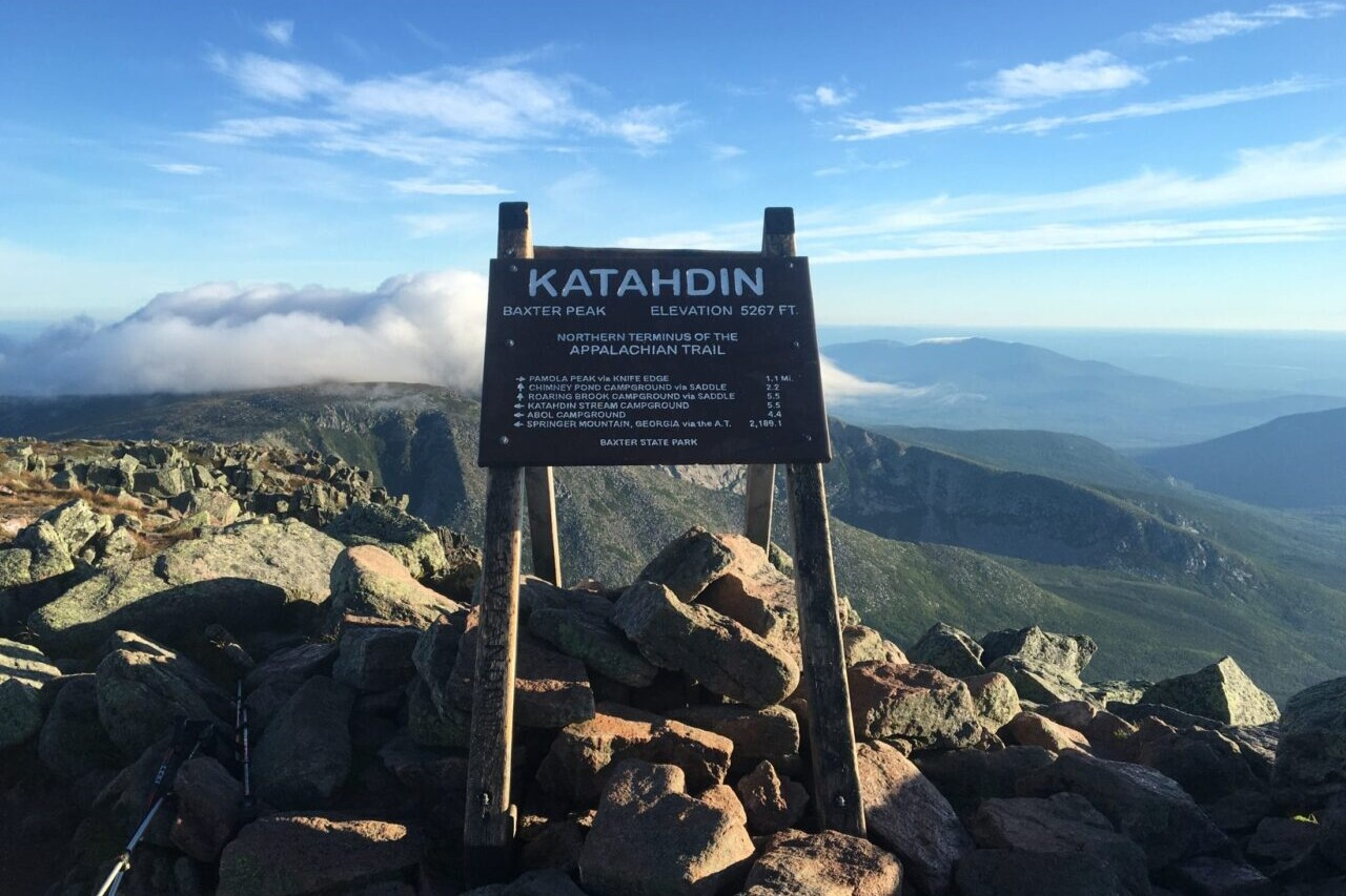 The summit sign for Mount Katahdin is silhouetted against a blue sky.