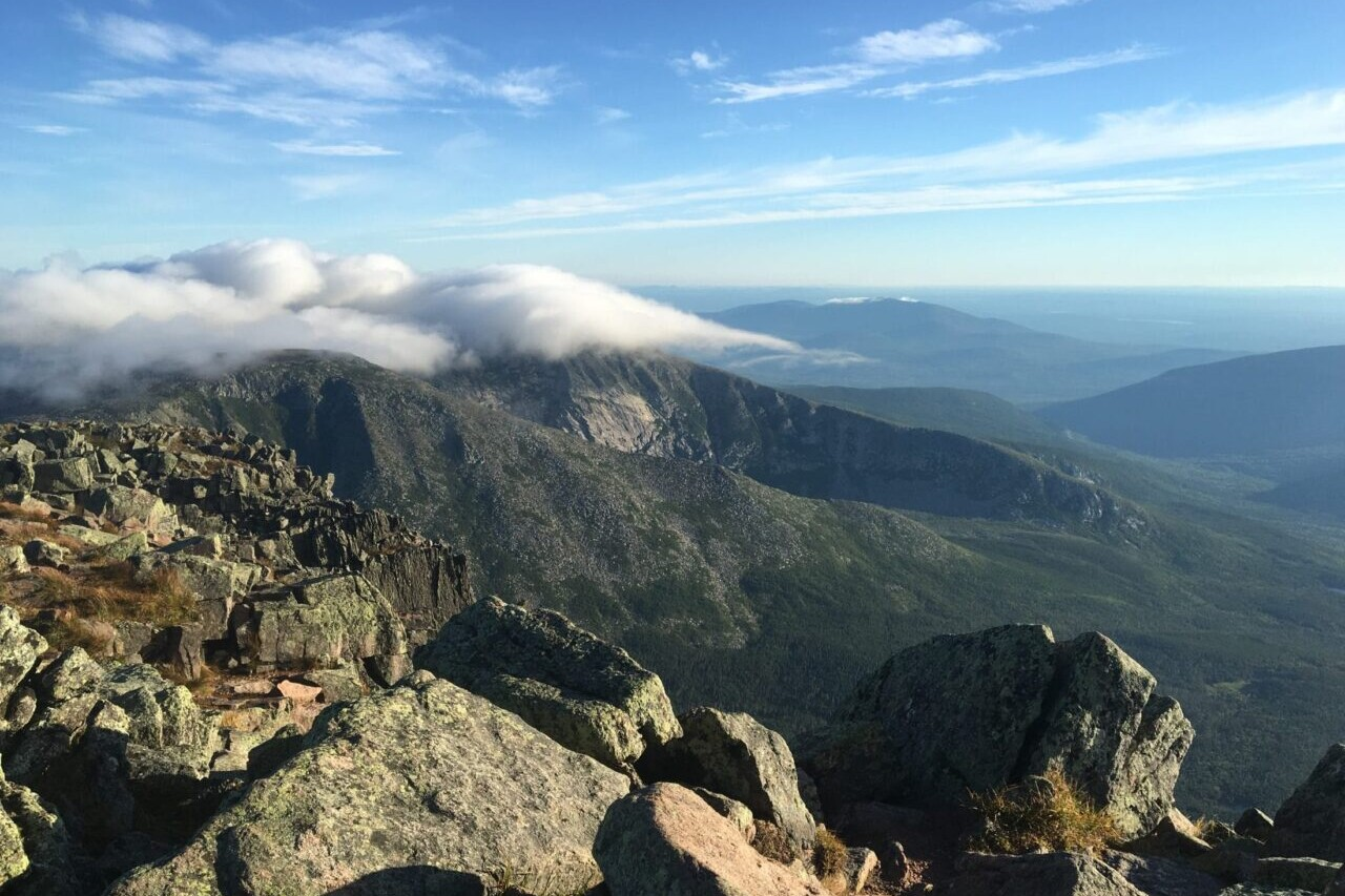 The view from Mount Katahdin shows distant mountains and rocky ridgelines.