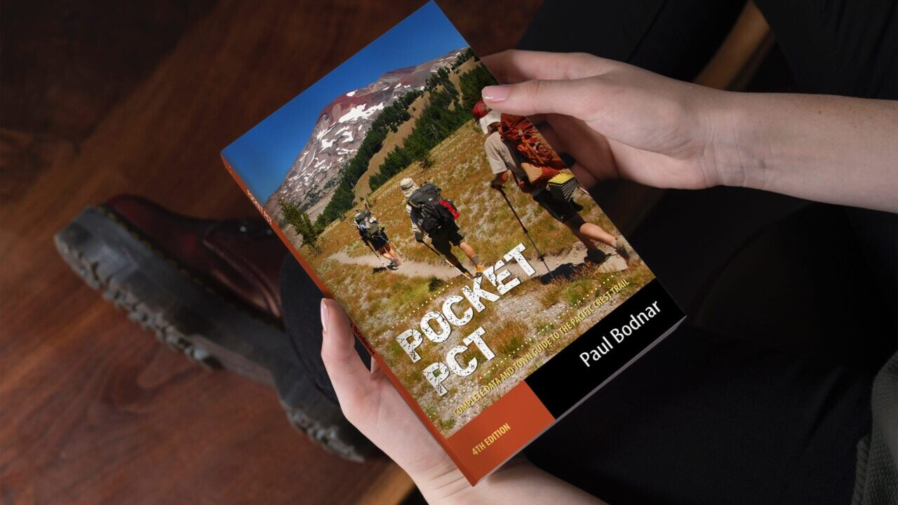 A person holds a copy of the Pocket PCT hiking guide book by Paul Bodnar.