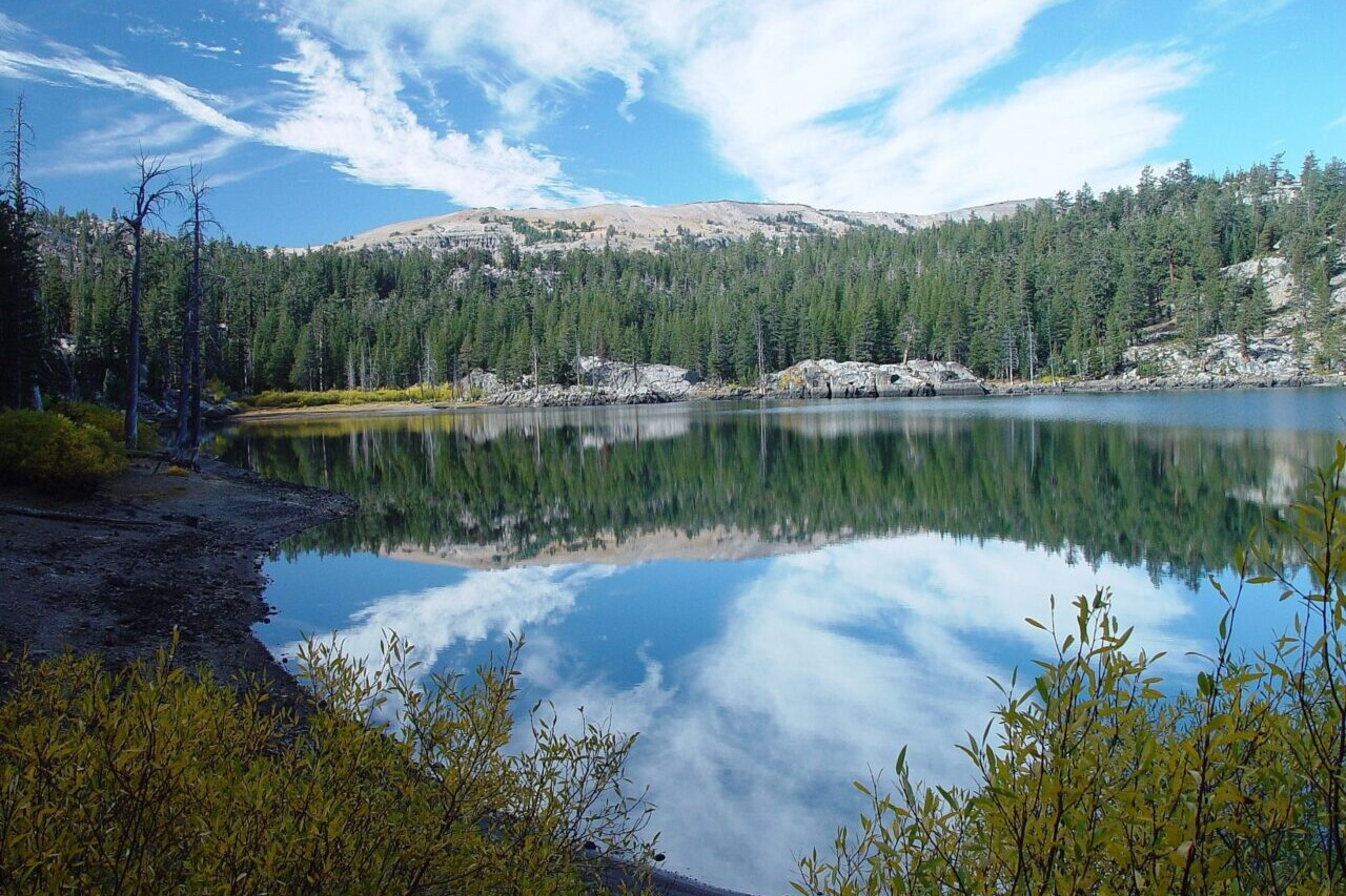 A lake reflects a nearby mountain, trees, and a blue sky.