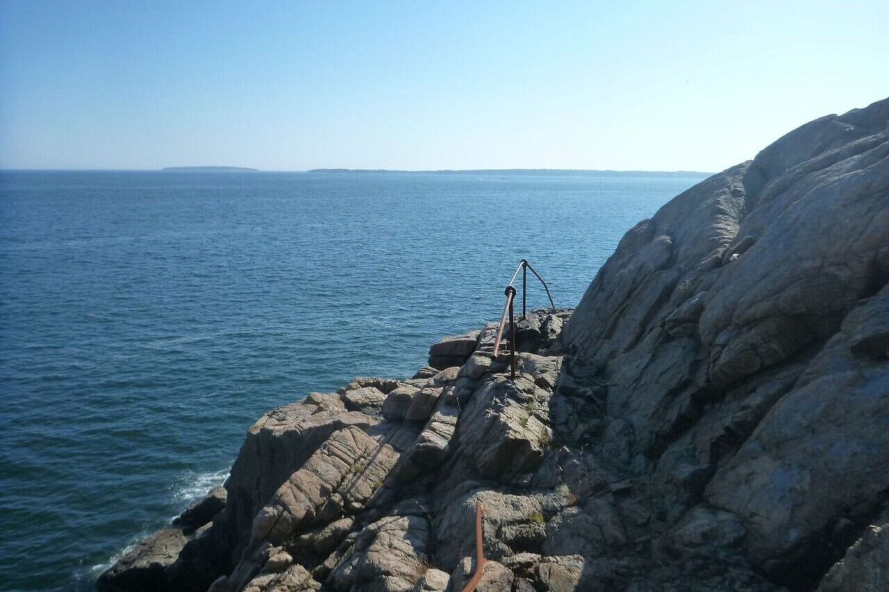 A trail winds around a rock outcropping on the edge of a large blue expanse of water.