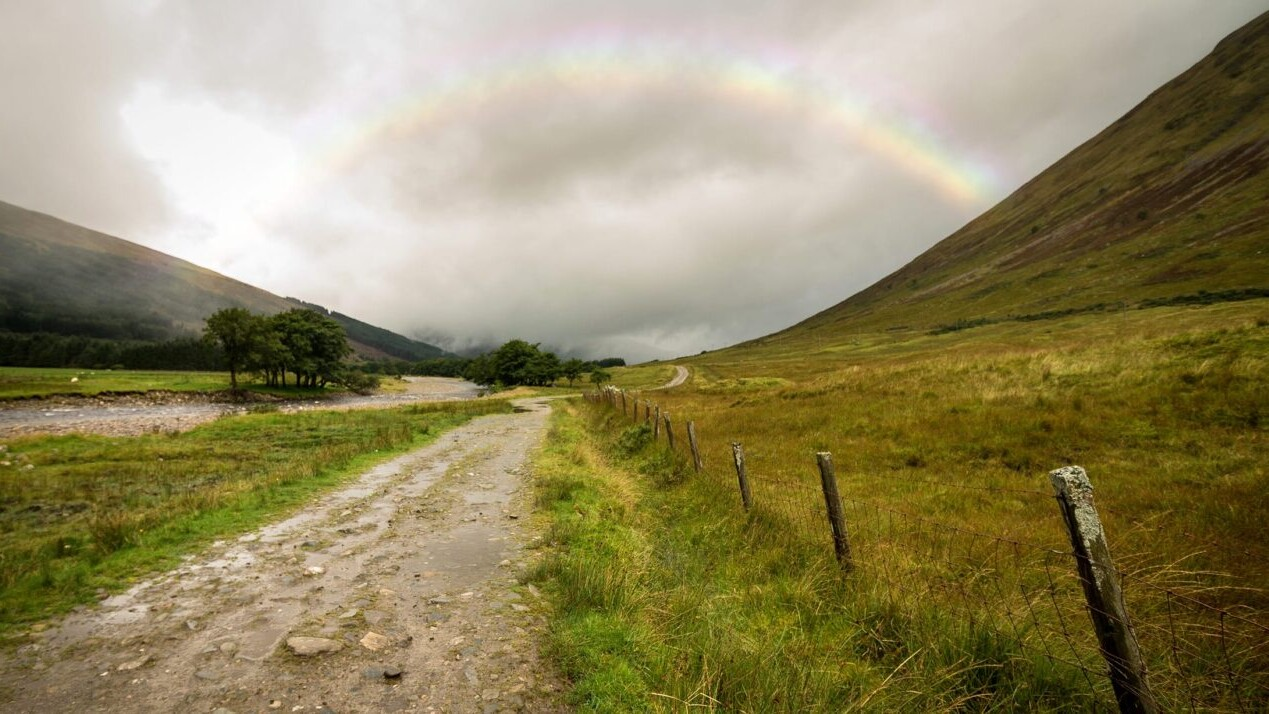 A rainbow appears over a rocky road cutting through a misty green landscape.