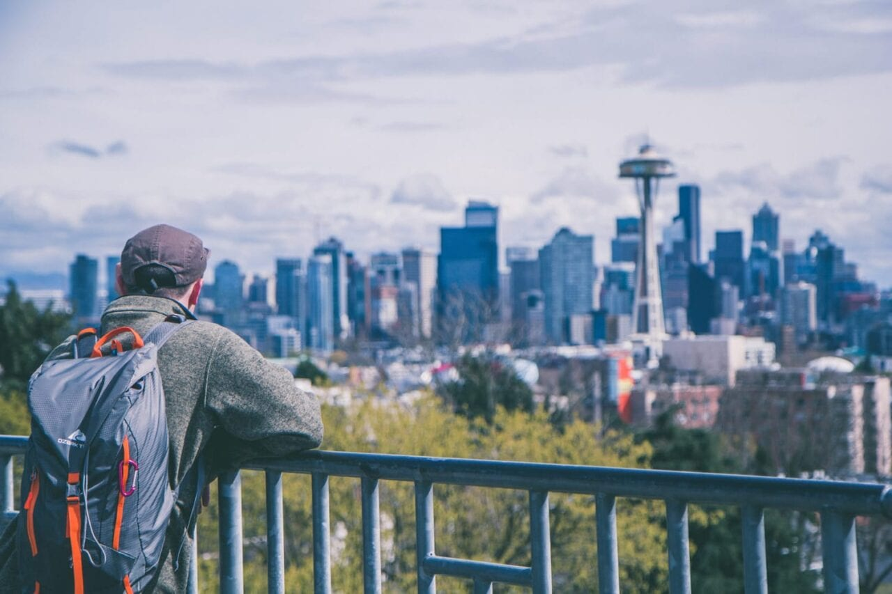 Man on bridge looking at Seattle Space Needle in distance