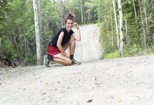 A hiker kneeling on a trail.