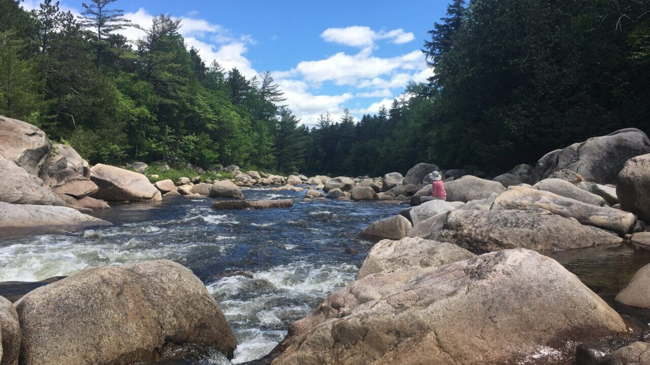Hikers on a rocky river in Katahdin Woods & Waters National Monument in Maine
