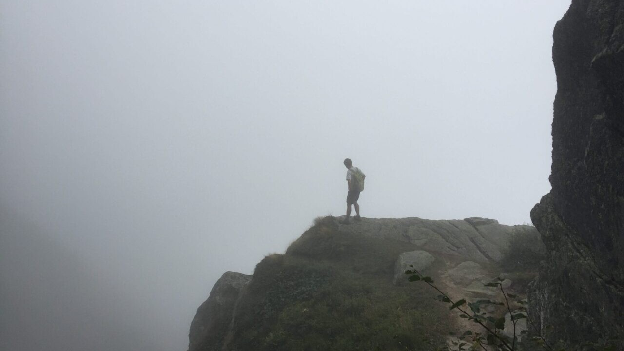 Hiker in the White Mountains on a foggy ledge