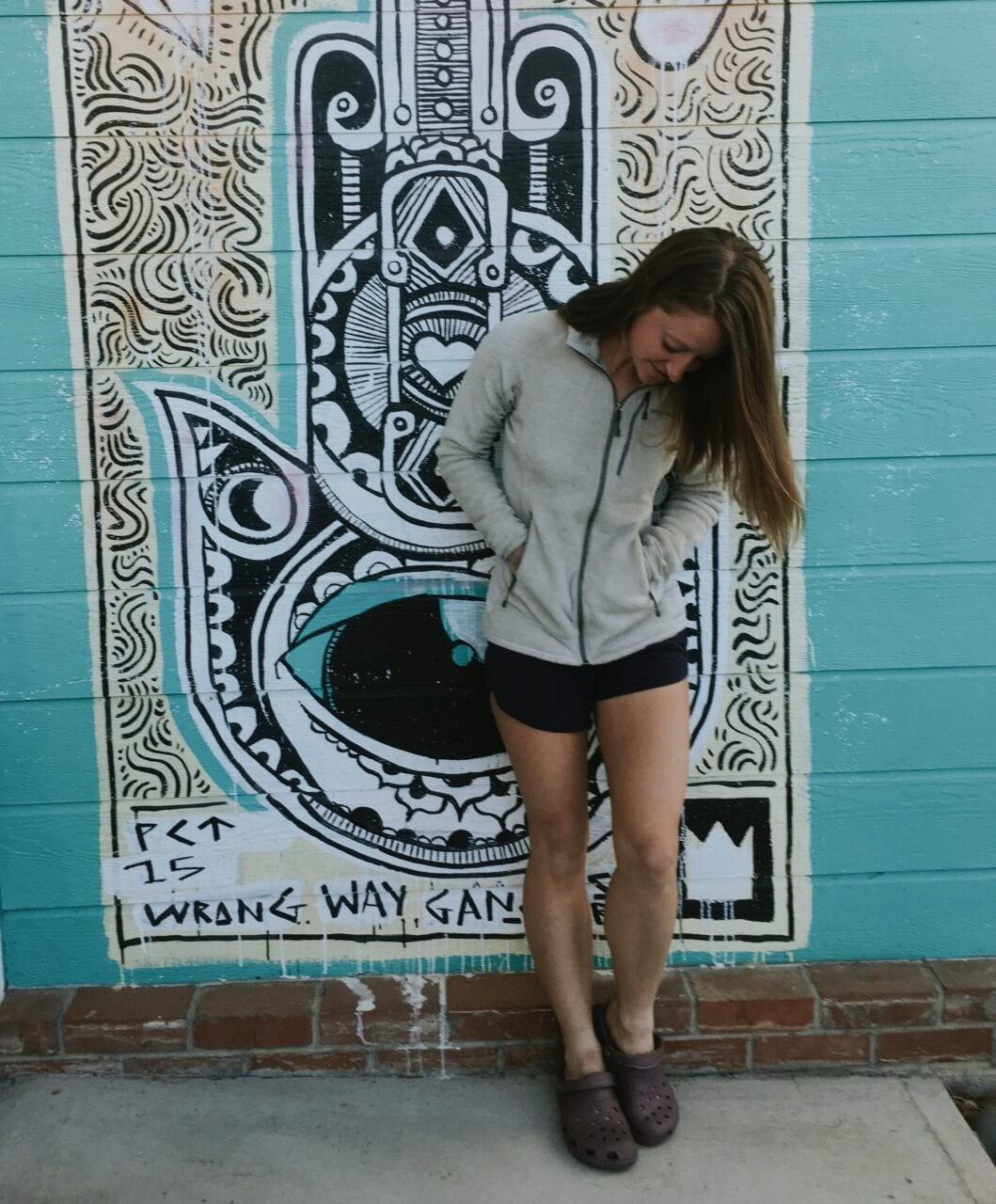 A woman posing against a wall with street art.