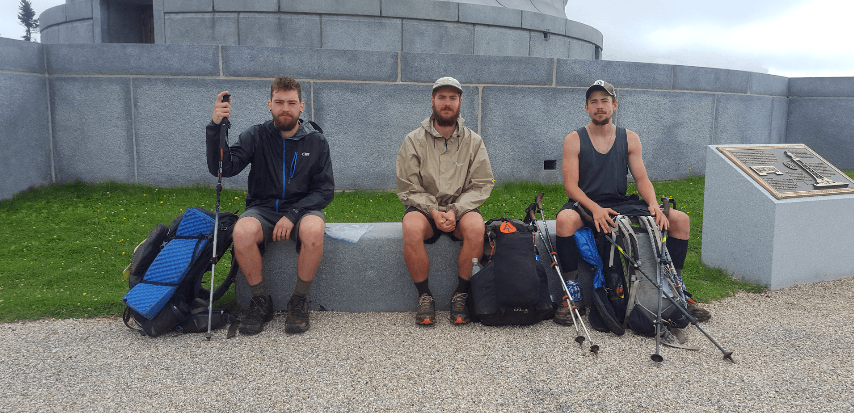 A group of guys hiking the Appalachian Trail sit on a bench with their backpacks.