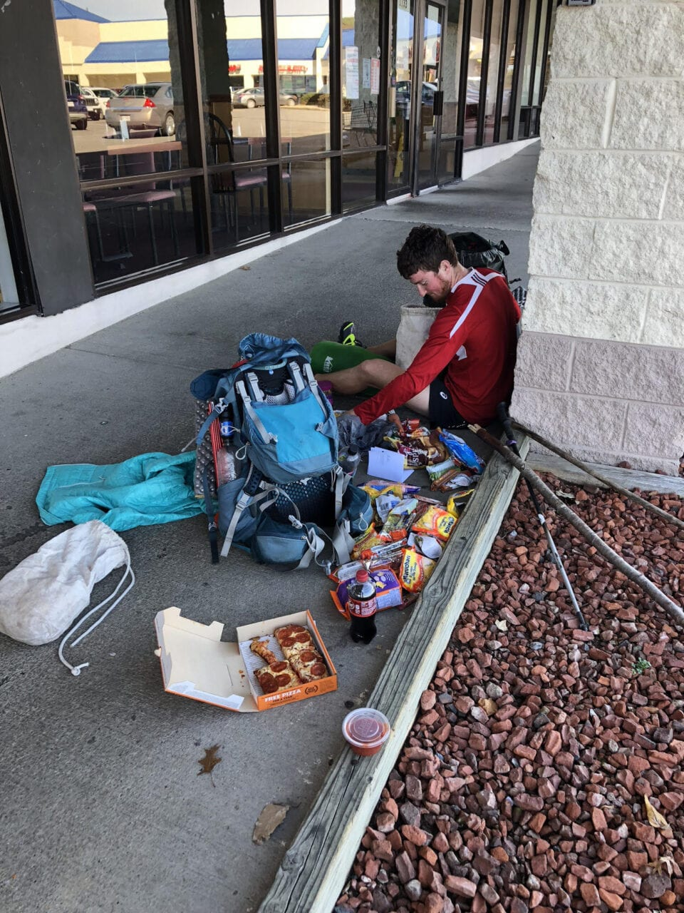 A thru-hiker sits on the ground eating with food spread out on the floor.