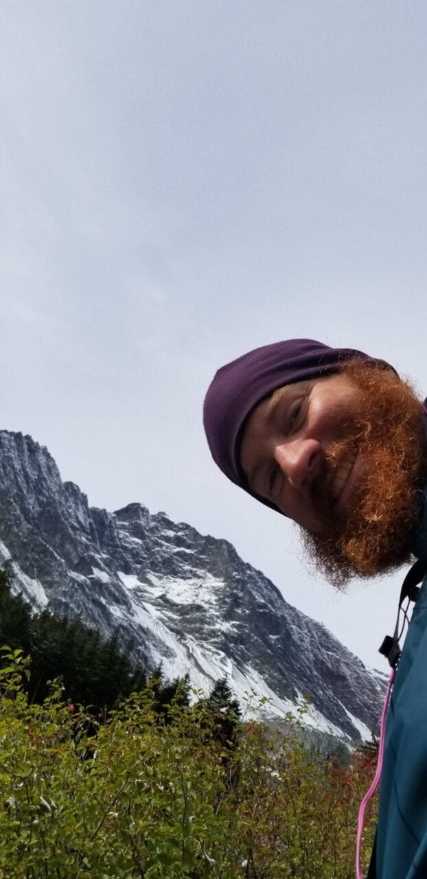 A man with a beard and a beanie smiles with a mountain behind him.