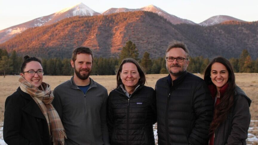 A group of people stand in a field in front of a snow-capped mountain.
