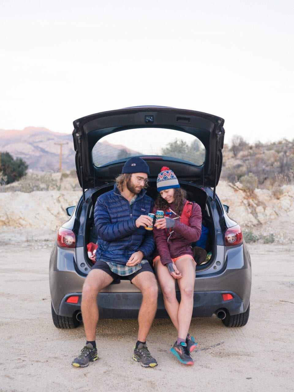 A man and woman sit in the trunk of a car cheers-ing their beers.