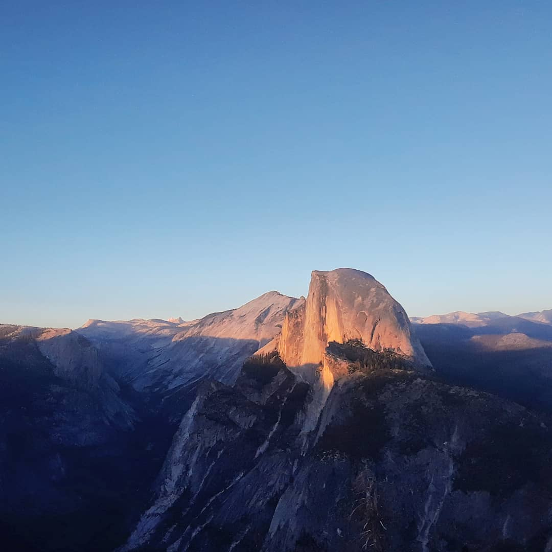 A view of a mountain peak during the sunrise.