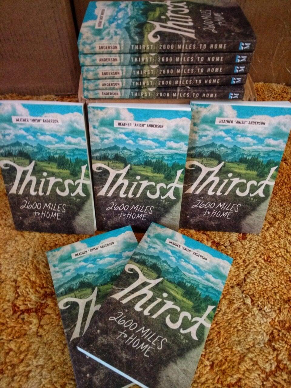 A stack of books called Thirst: 2600 miles to home by Heather Anderson.