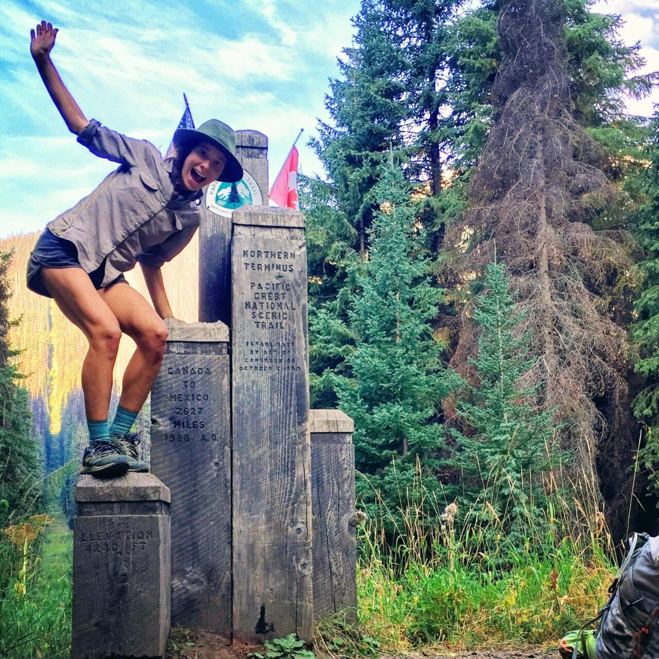 A woman hiker stands on the northern terminus of the Pacific Crest Trail.