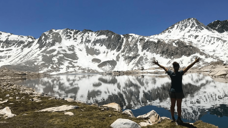 A woman stands in front of a lake by some mountains.
