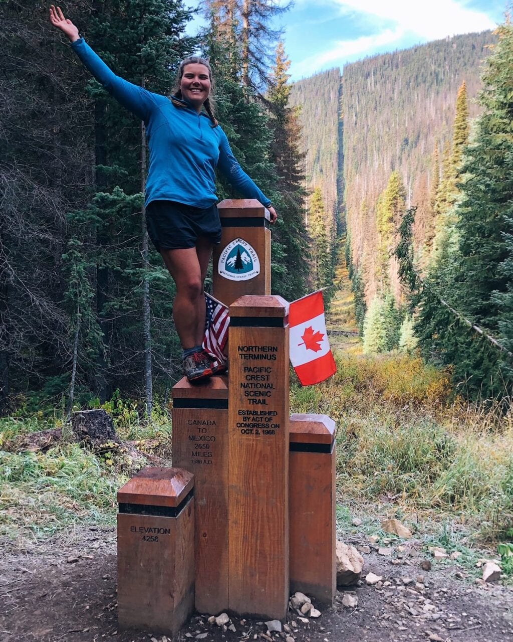 A woman hiker standing on the northern terminus of the Pacific Crest Trail.