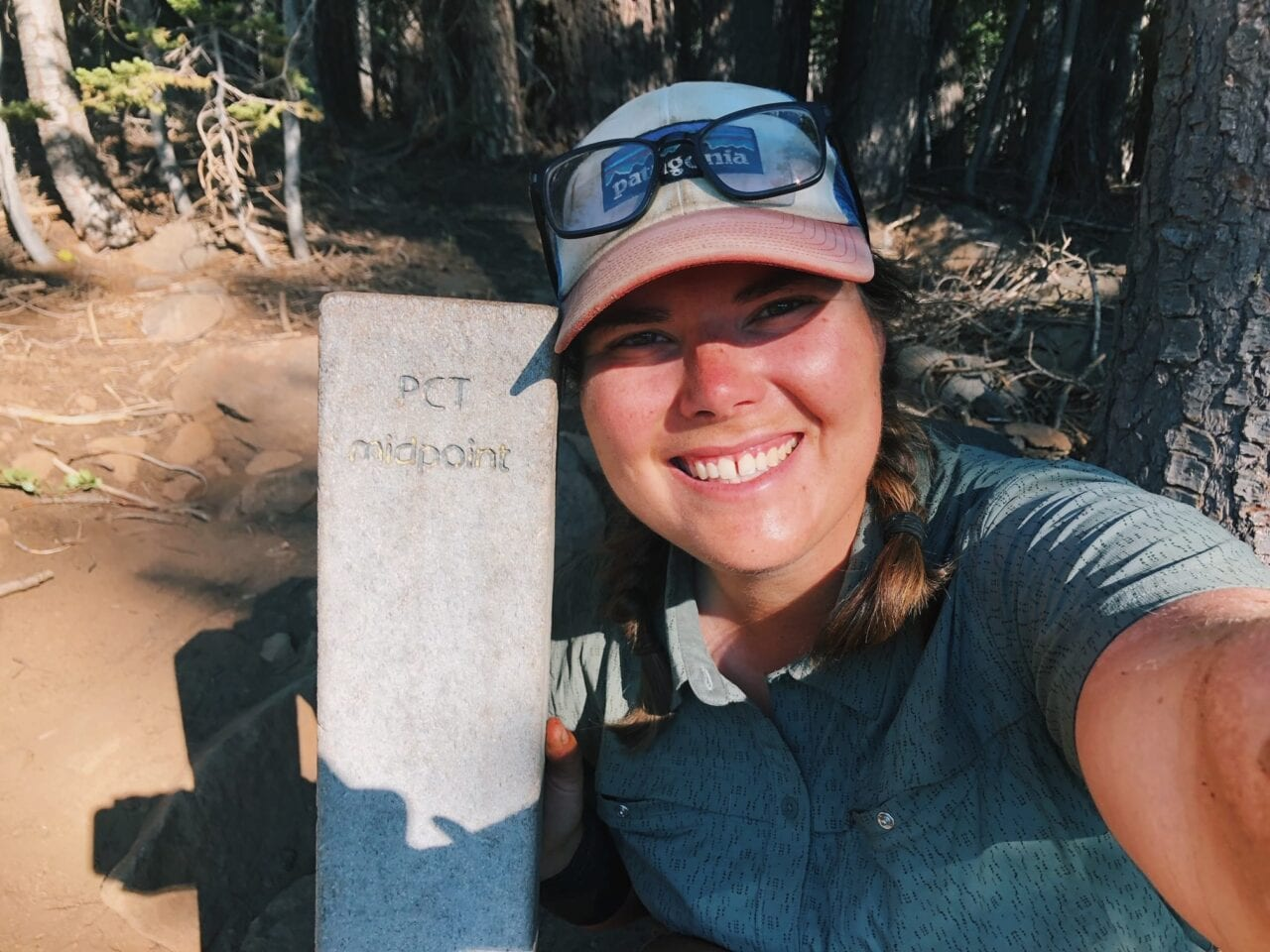 A woman hiker smiling next to a PCT trail sign post.