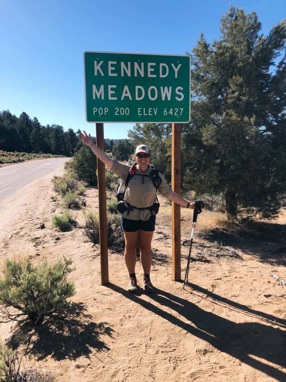 A woman stands next to a Kennedy Meadows sign with her hiking backpack and trekking poles.