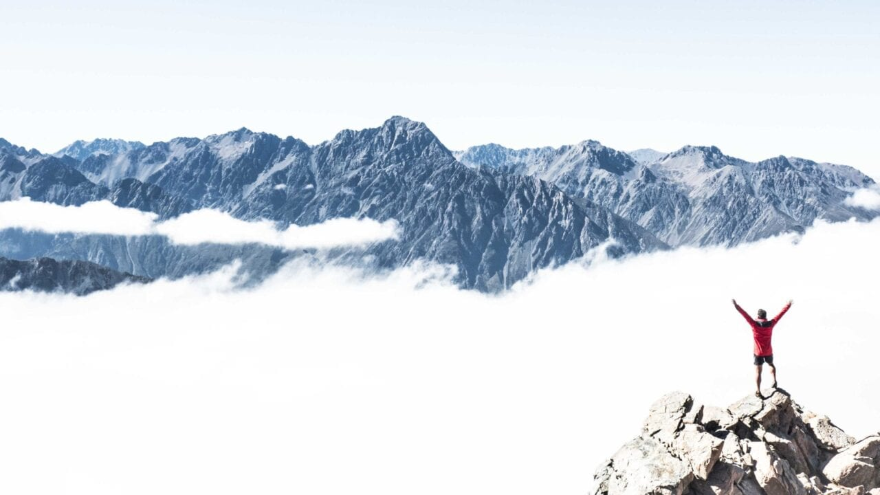 A man in red standing on a mountain above the clouds with his arms in the air.