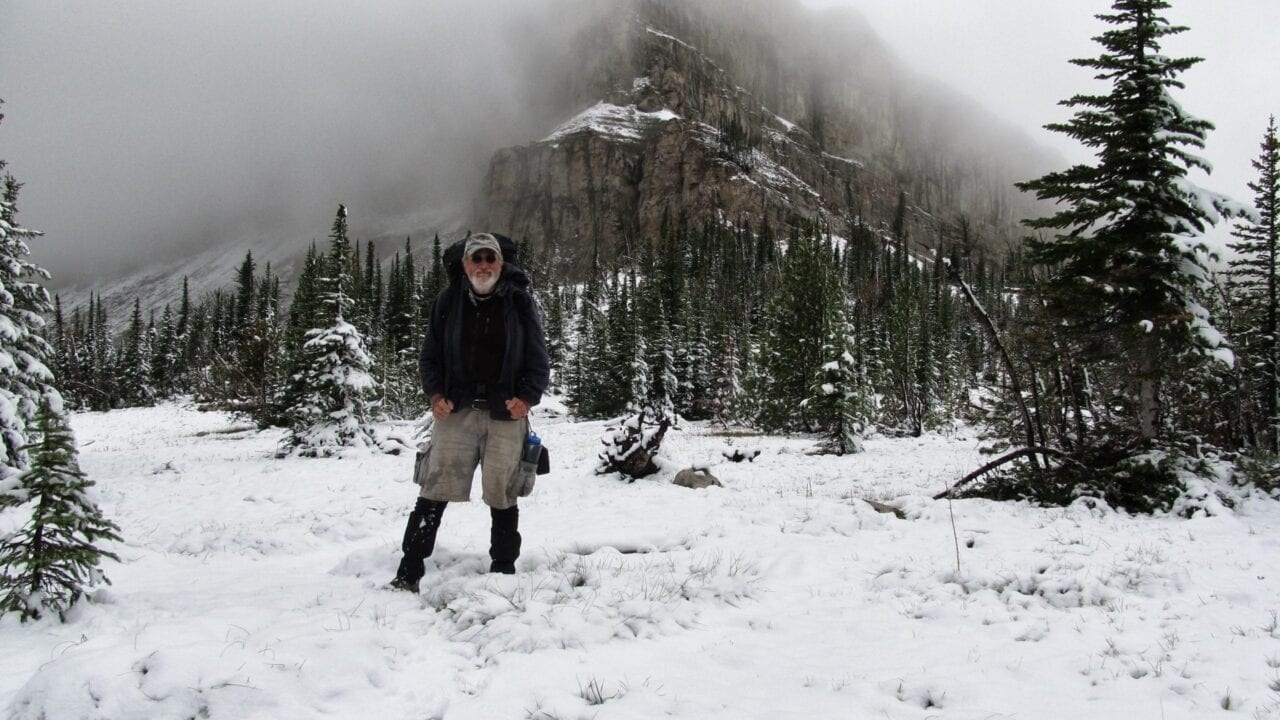 A man standing in the snow with a mountain and trees in the background.