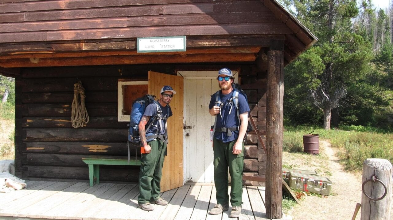 Two USFS firefighters standing at a guard station.