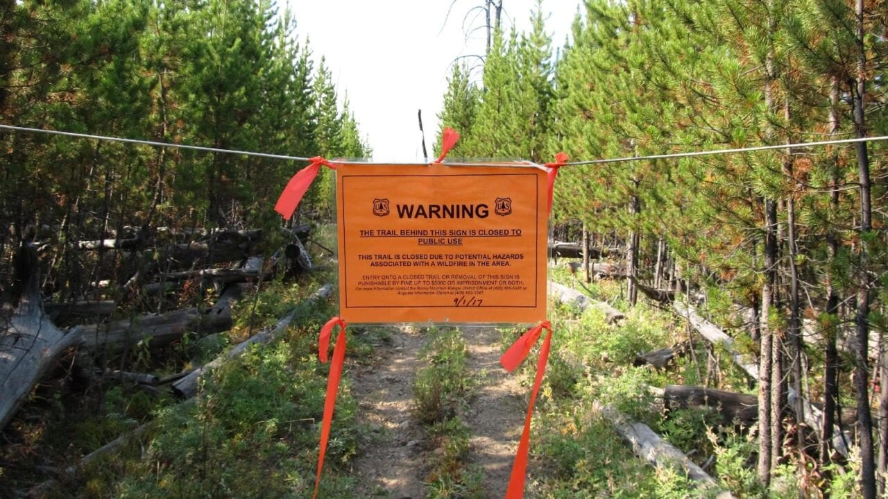 A warning sign hung to close off a trail.