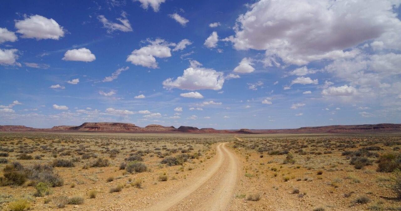 A jeep road extends through a desert landscape towards distant mountains on the Wild West Route.