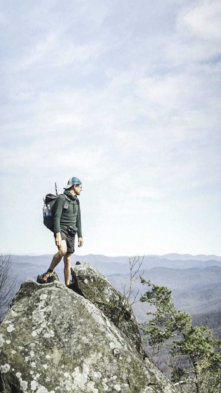 A hiker standing on a big boulder looking out at the scenery.