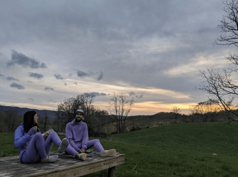 Two hikers in purple clothes sitting.