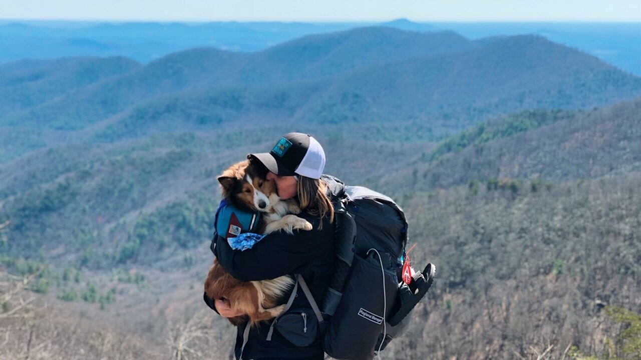 A girl hugging her dog on the Appalachian Trail.