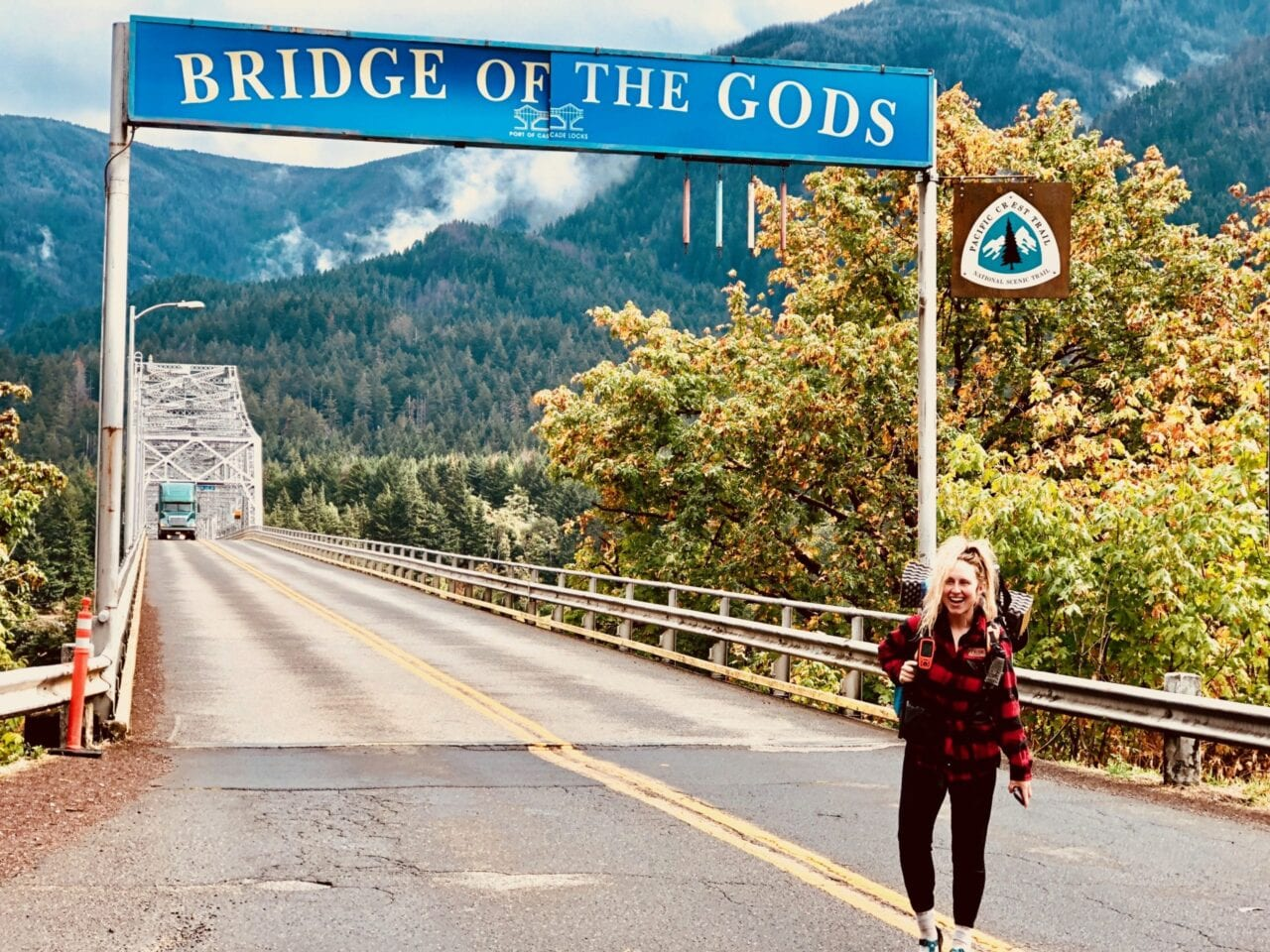 A woman standing in front of the Bridge of Gods sign.