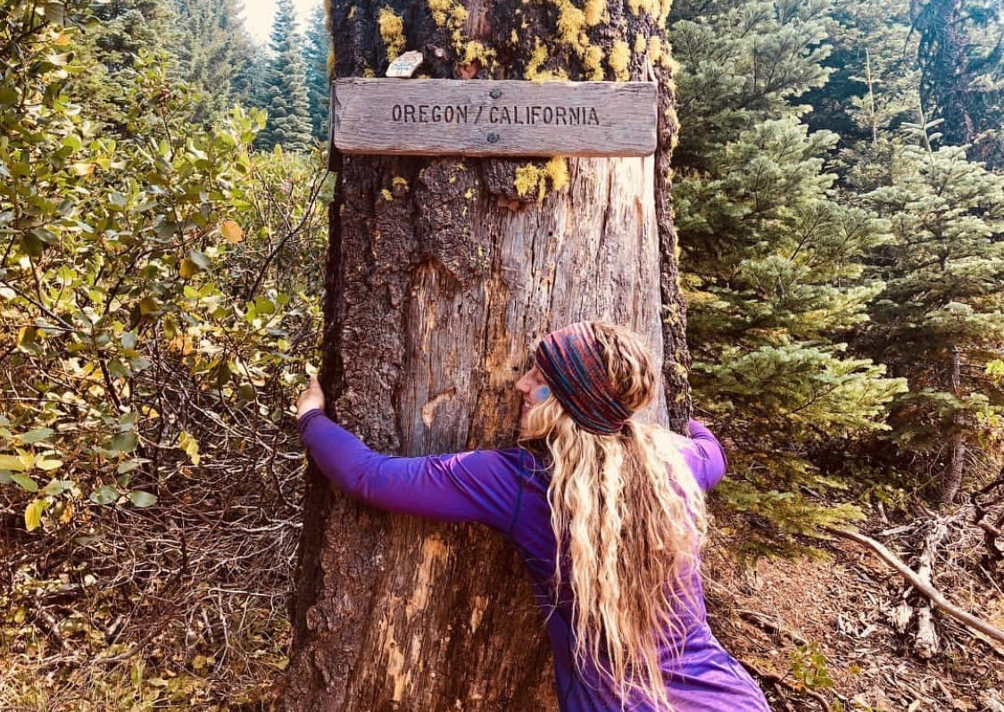 A woman hugging a tree.