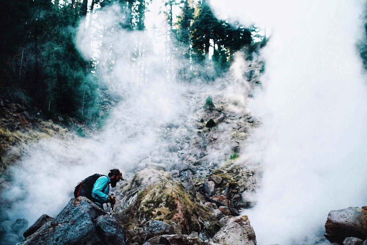 A hiker wearing a blue shirt climbs up a misty rock face.