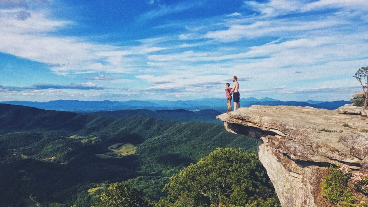 A man and woman stand on a cliff on the Appalachian Trail.