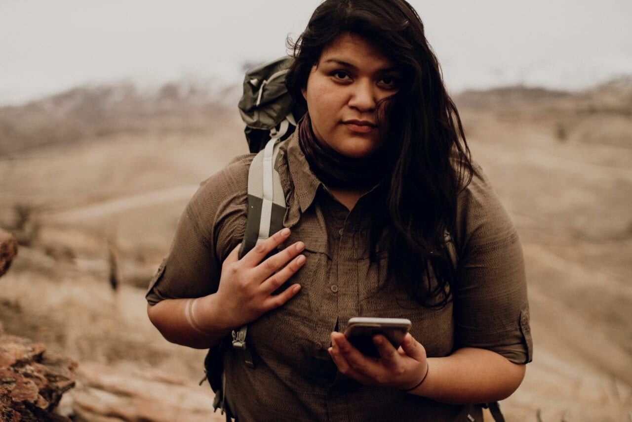 A hiker wearing a brown shirt holds a mobile phone.