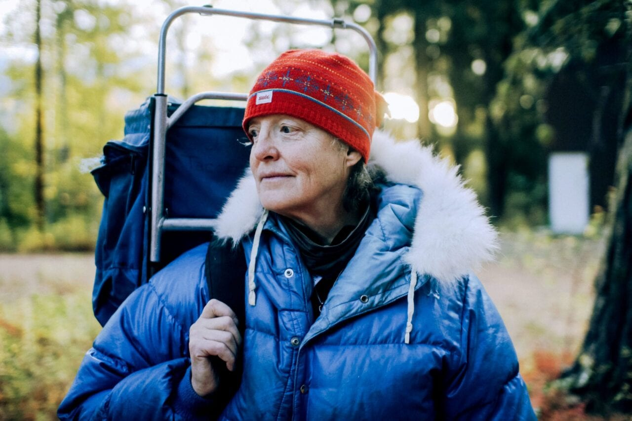 A hiker wearing a blue jacket and a red hat carries an external frame backpack.